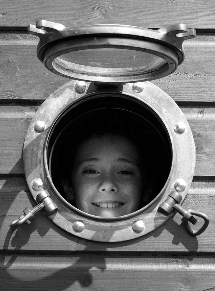 Portrait of young boy looking out through a porthole