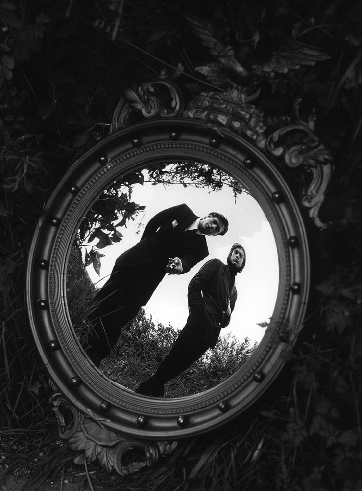 Reflection of two men in an ornate mirror
