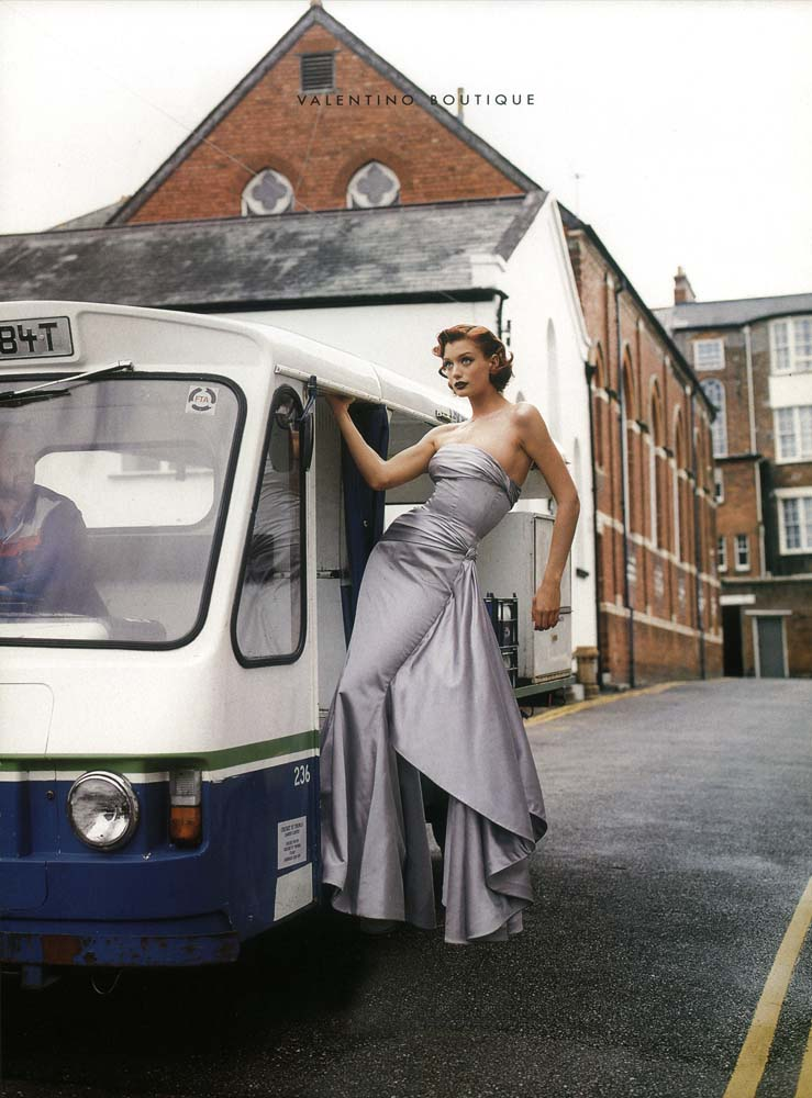Valentino gown worn by model hitching a lift on a milk cart