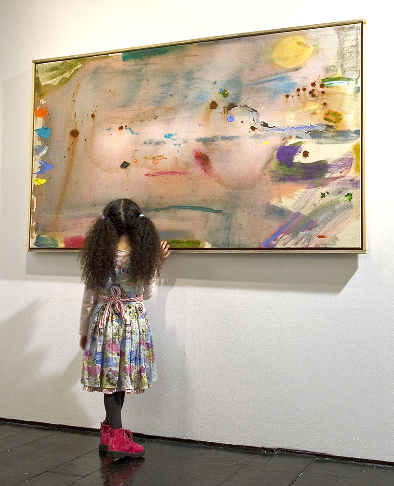 Young girl looking at abstract painting