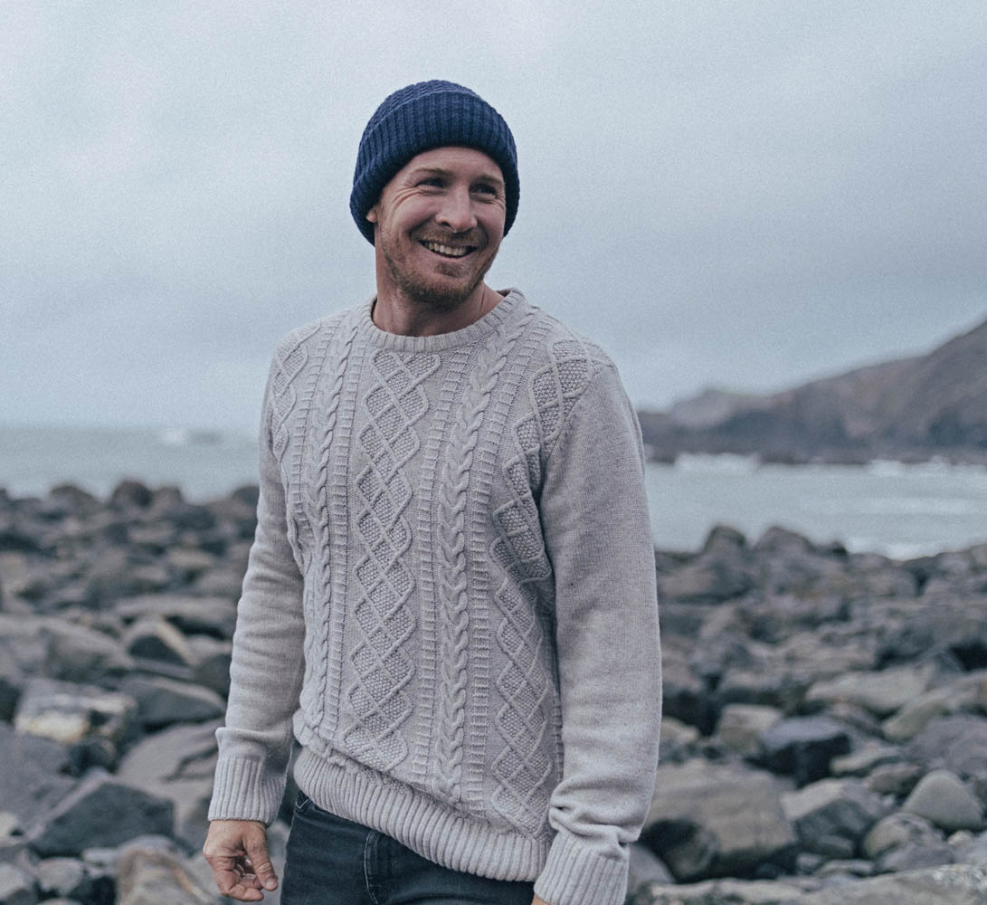 Andrew Cotton wearing a cable sweater on a rocky shoreline